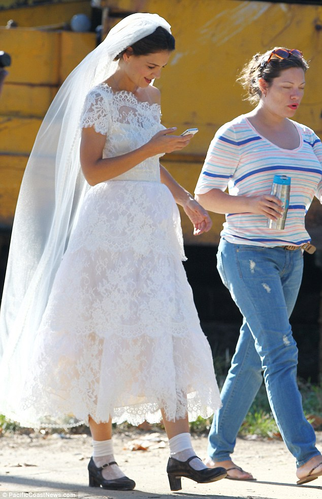 Bringing back memories? Katie donned a frilly white wedding dress while on location on Friday