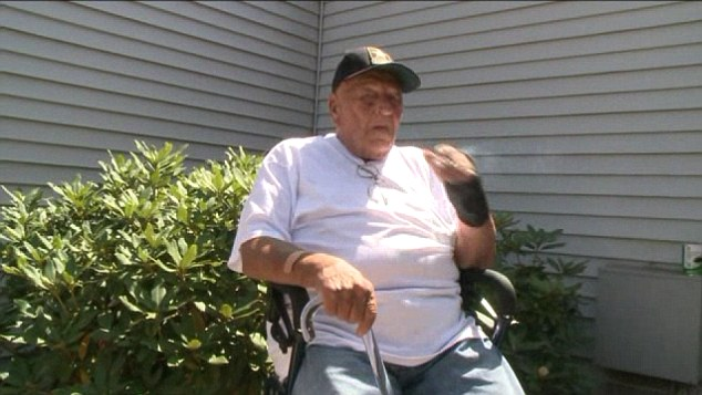 War hero: Andy Nowicki enjoys a cigarette in front of the apartment from which he and his wife faced eviction, but now they have struck a deal with administrators to allow them to stay