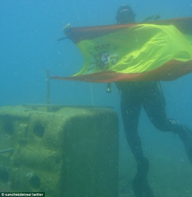 Incursion: A Spanish police diver hold up the Spanish flag while inspecting one of the concrete blocks dropped by the Gibraltan government off the coast to encourage marine life