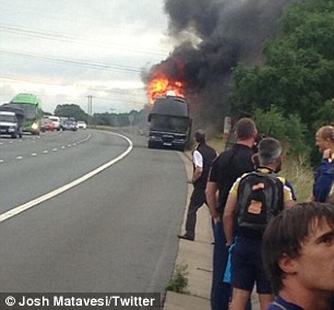 Inferno: Worcester's bus is marooned on the hard shoulder of the M5 as players wait alongside the motorway