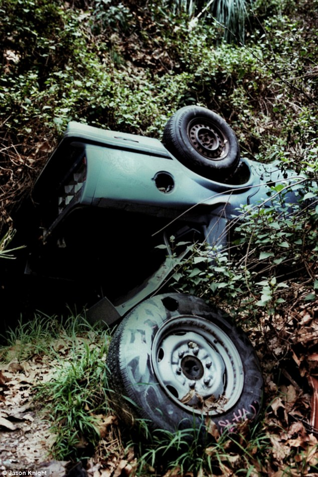 Rolled: A car rests on its roof, with its trunk popped open and a discarded tire near by