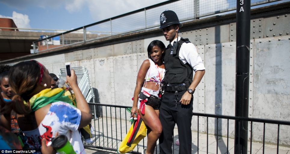 Good fun: A reveller poses for pictures with a police officer
