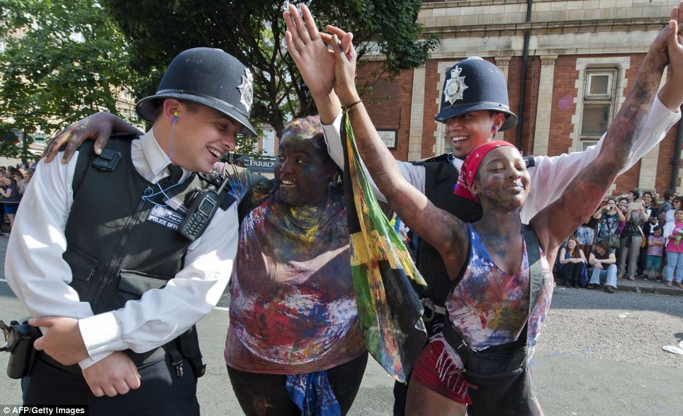 Light hearted: The festivals' lively atmosphere seems to be infectious as the officers laugh along with the dancers