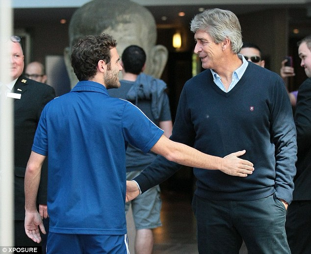 Coincidence? Manuel Pellegrini saying hello to Juan Mata as the two passed one other