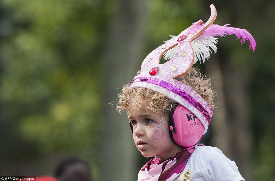 A young child wearing a feathered head-dress and ear protectors watches the first day of the Notting Hill Carnival, sound levels are expected to hit 140db at Adults Day today