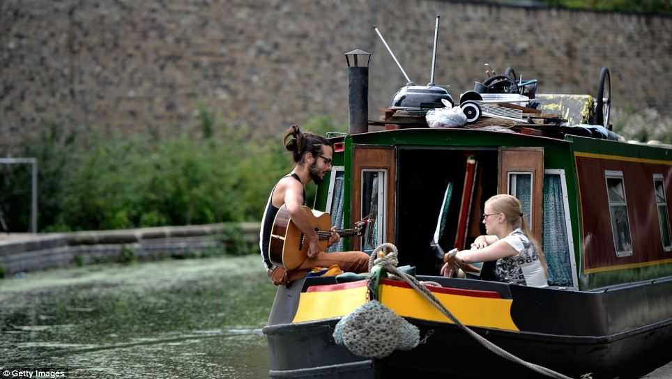 Sunshine serenade: A man and woman enjoy the warm weather from a house boat in North London