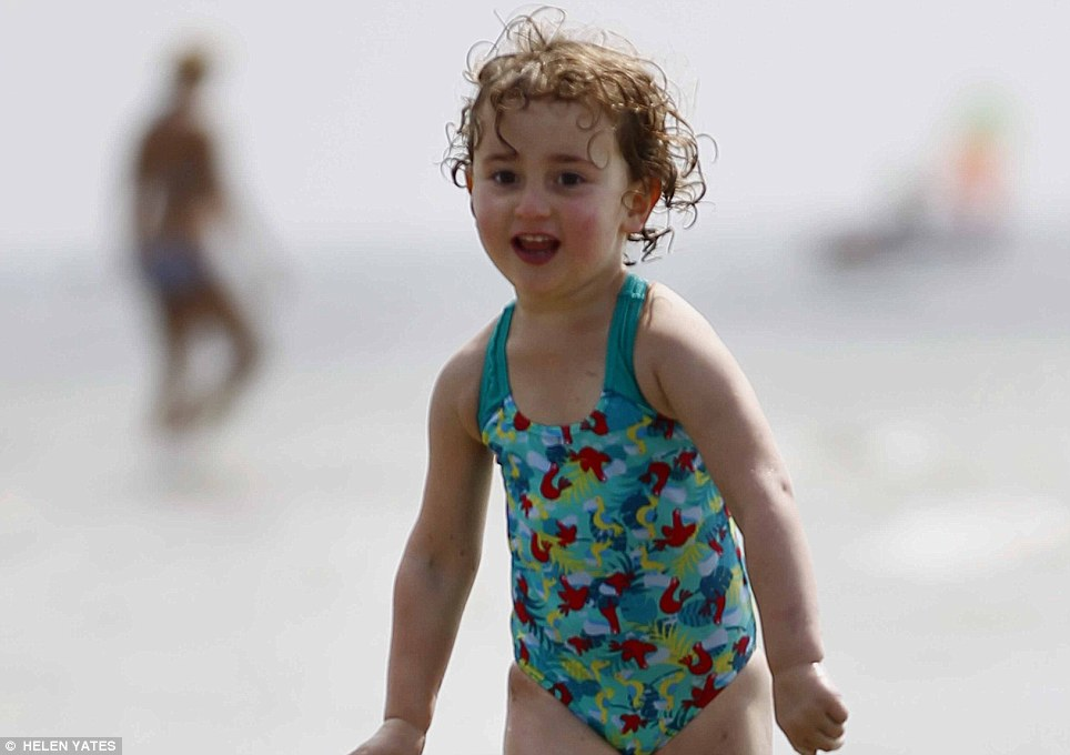 Eden Malenchini (4) cools off in the sea as thousands gather on West Wittering Beach, West Sussex