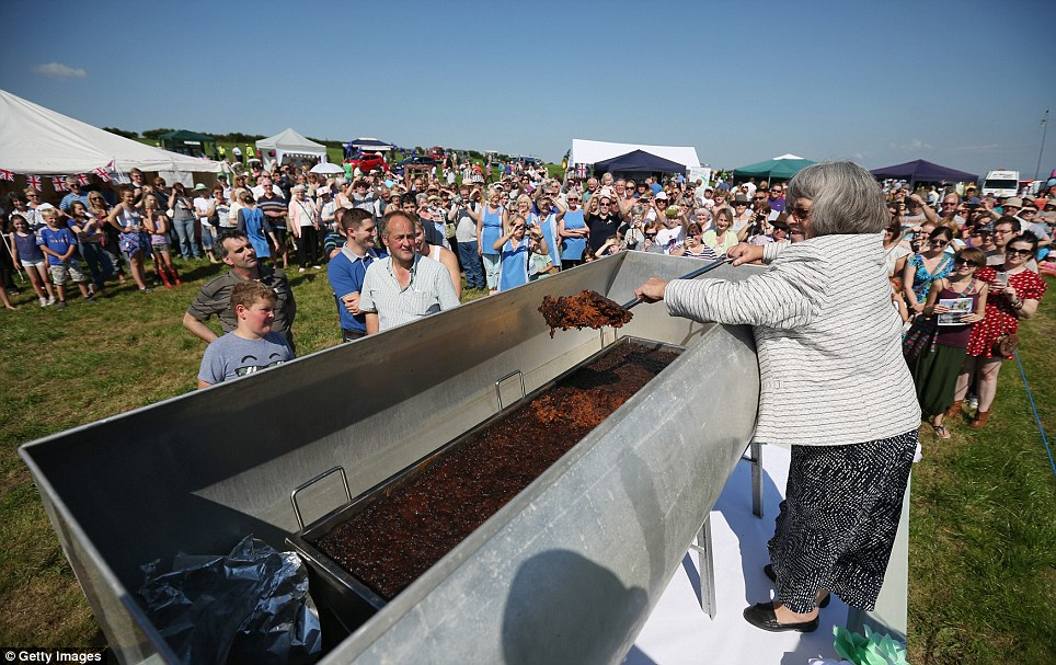 Sweet sunshine: Mitzi Hayhurst, the President of the the Aughton Pudding Festival, makes the first slice of the pudding with a ceremonial spade