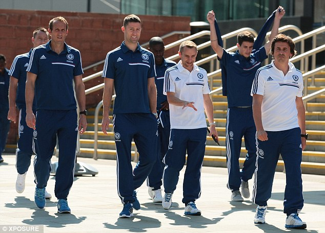 Happily walking: Gary Cahill among the Chelsea backroom staff