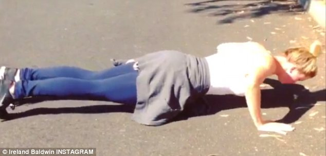 Watch out for traffic: Push-ups are also a big part of Baldwin's exercise regime and she hit the floor on a residential street