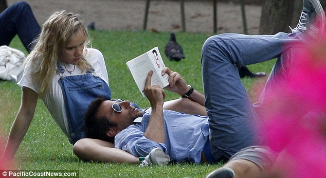Relaxed: Bradley looked very at ease as he lay in his girlfriends lap to read