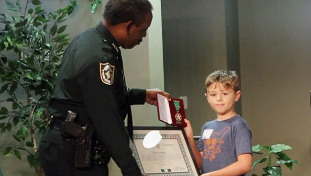 Nine year-old Ethan Temmen receives his award from Orange County Sheriff after saving the life of a toddler in Florida
