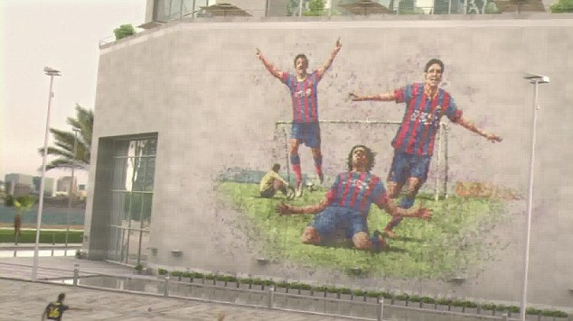 Picture perfect: Andres Iniesta and Sergio Busquets create this image by kicking a football at a wall