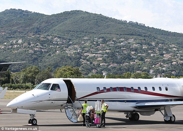 We hope you enjoy your flight with Cowell Airways: Airport staff load the plane with luggage