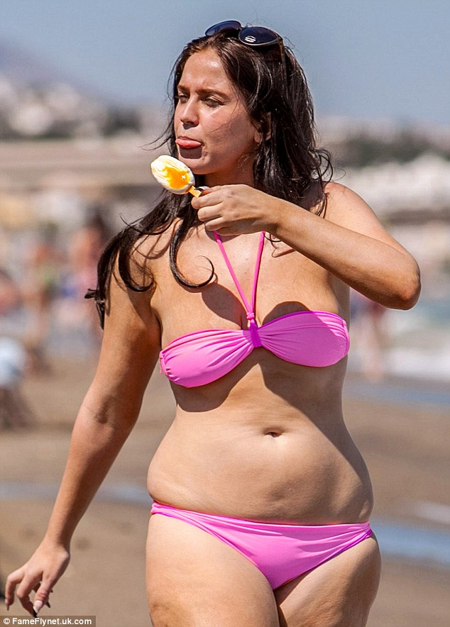 Vicki Pattison tucks into an ice-lolly as she strolls across the sand