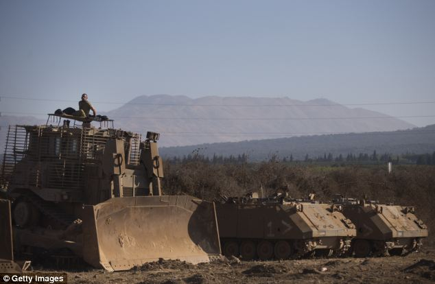 A soldier sits on top of an army bulldozer as Israeli troops take part in training