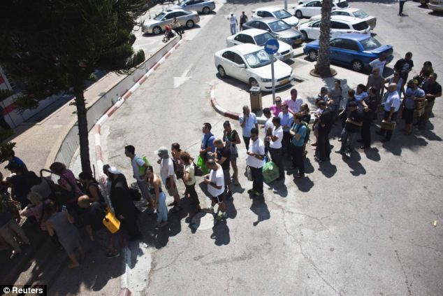Israelis queue outside a gas mask distribution point in Tel Aviv
