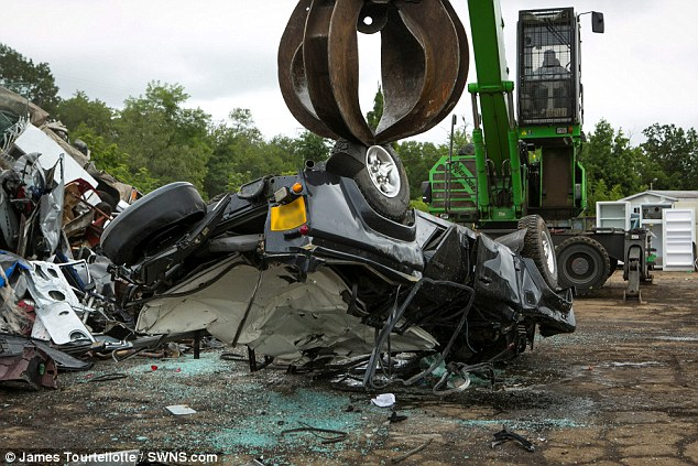 Worthless: The scrap metal worker dumps the battered vehicle upside down