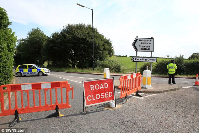 Road closed: Police block access to the site as firefighters continued to battle the fire yesterday