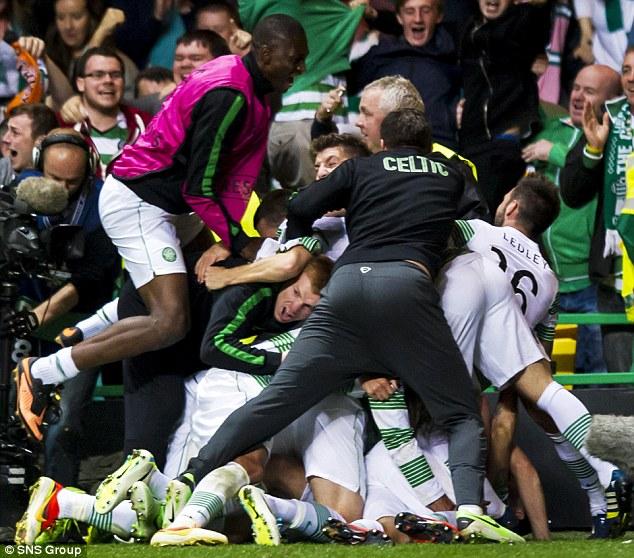 Pile on: Celtic manager Neil Lennon joins in the celebrations after Forrest scored