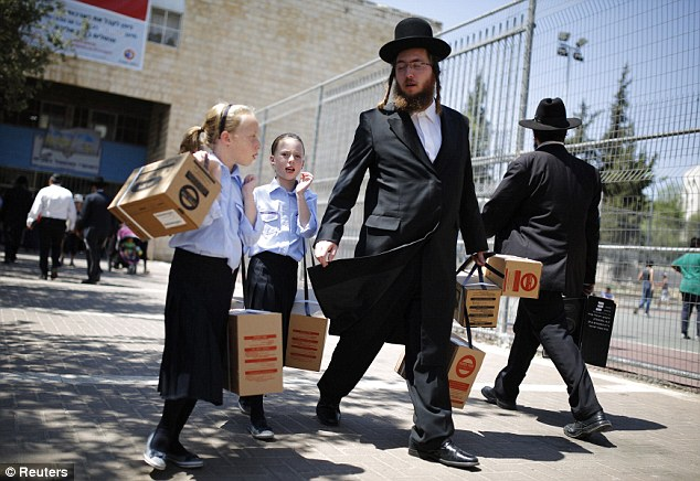 Panic stations: An ultra-Orthodox Jewish man walks with his children after collecting gas masks at a distribution point in Israel as fears grow that strikes by the U.S. and Britain on Syria could trigger all-out war