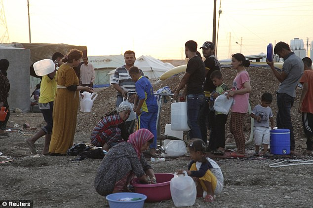 Escape from Assad: Syrian refugees use containers to collect water at the Arbat refugee camp in the northern Iraqi province of Sulaimaniya after fleeing the violence in their native country