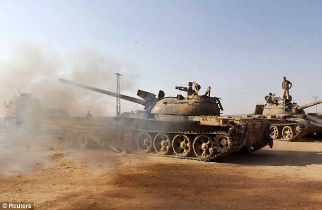 Dusty landscape: Free Syrian Army fighters drive a military tank that belonged to forces loyal to Syria's President Bashar al-Assad after they seized it, in Aleppo's town of Khanasir
