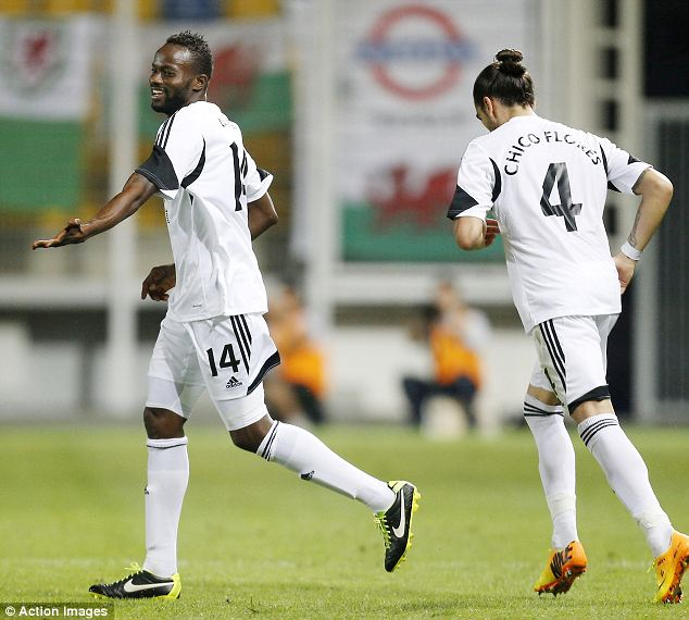Timely reminder: Roland Lamah (left) celebrates after scoring the first goal for Swansea