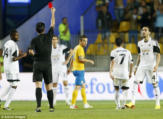 Off you go: Leon Britton of Swansea is sent off by referee Michail Koukoulakis