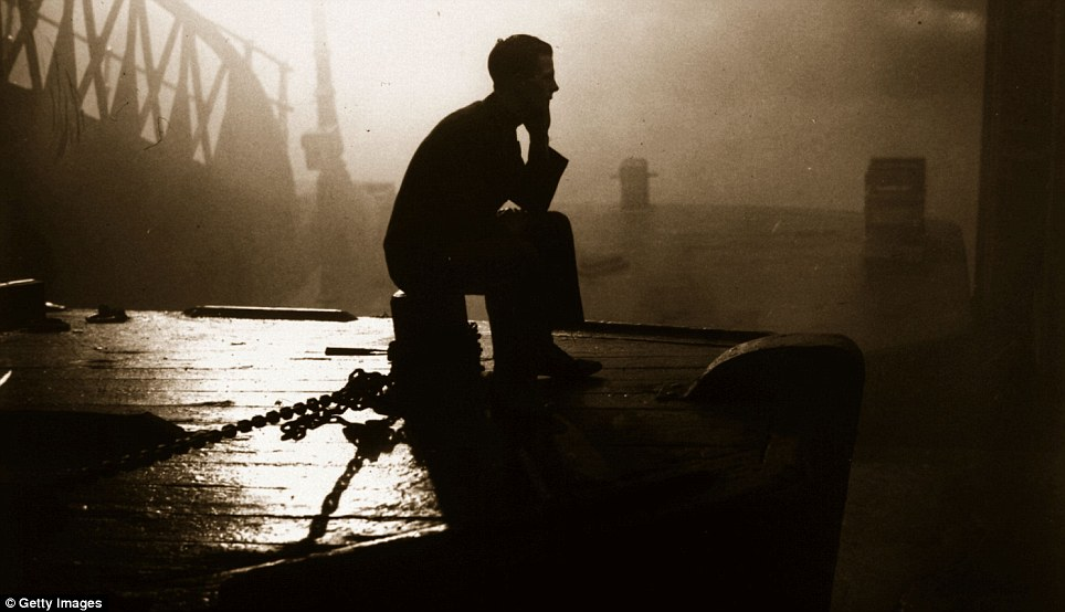 A bargee sits on the stern of his barge waiting for the London fog to lift before he can start work