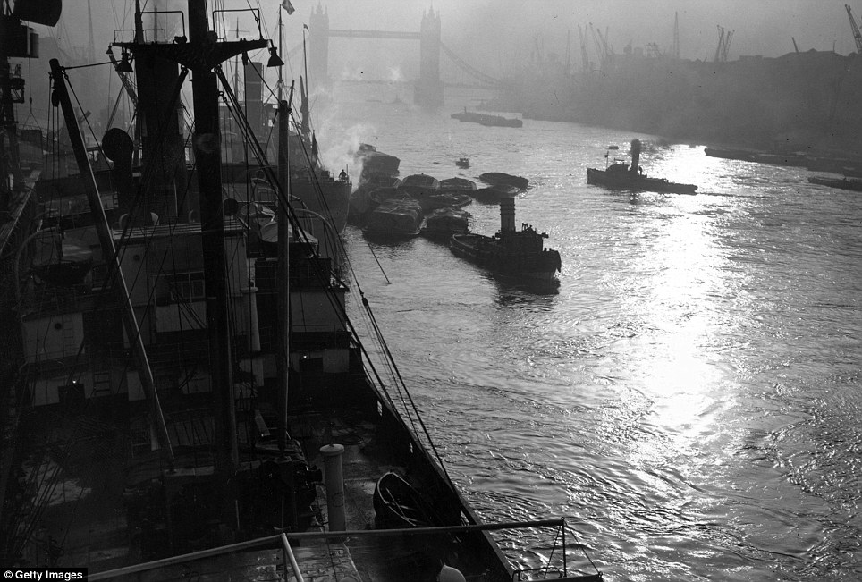 26th October 1938: Heavy fog brought ships to a standstill in their moorings on the River Thames at the Pool of London before a ray of sun pierces through the smog allowing them to go on with their business