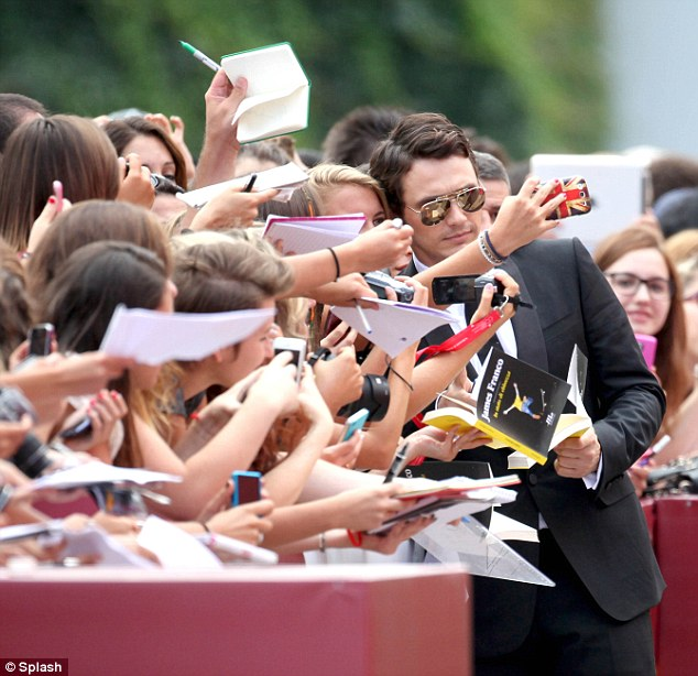 Getting involved: The actor immersed himself in a sea of female fans, signing autographs for the excited bunch as he took a break from red carpet duties