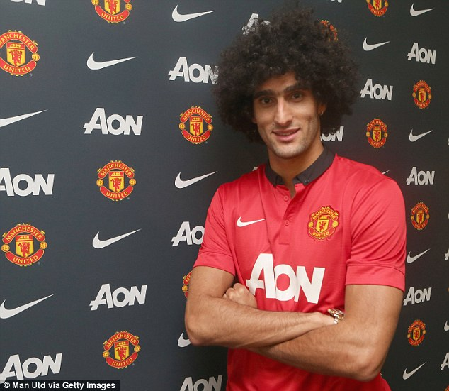 New man in town: Fellaini poses in a Manchester United shirt