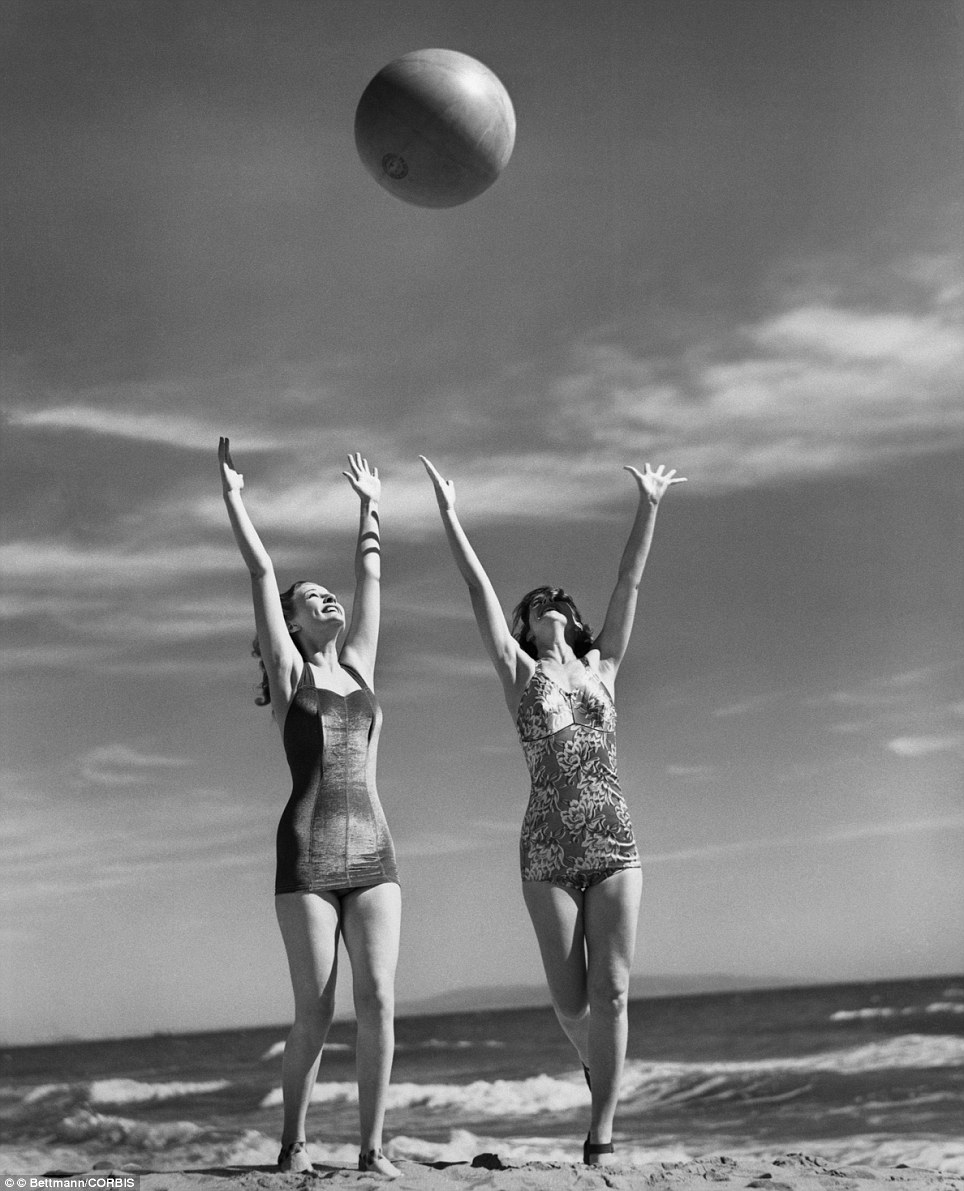 Mary Howard and Ann Morris show of some early 1940s-style swimwear as they frolic with a ball in the summer of 1941