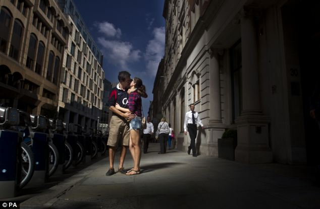 A couple kiss as the sun reflects off the Walkie Talkie building, in Fenchurch Street, in central London