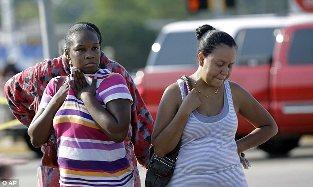 Worried sick: Parents,  Eunice Pacheco, right, and LaKesia Brent, left, wait for news about their children outside Spring High School