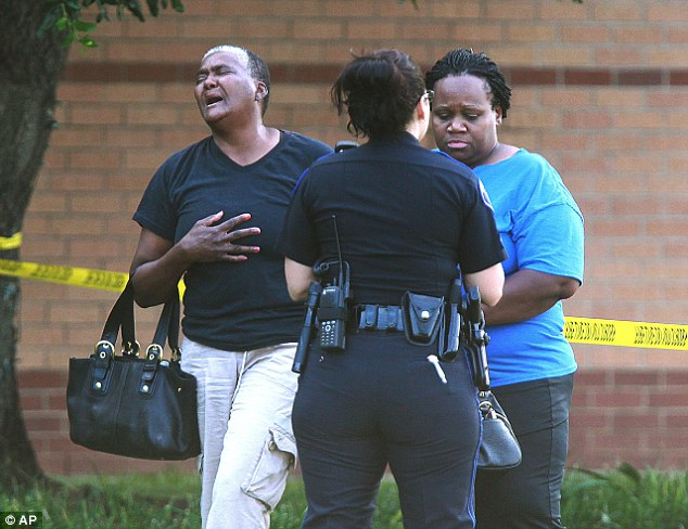 Raw emotions: A pair of women react after a stabbing during a fight involving multiple students inside Spring High School