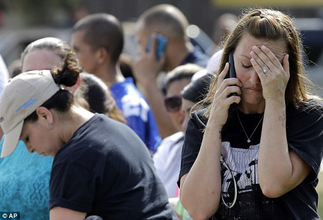 Heartbreak: Laurie Garza talks on the phone as she waits for her daughter outside Spring High School