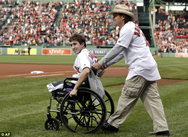 Together: Bauman is wheeled out by Arredondo to throw out the first pitch at Fenway Park on May 28