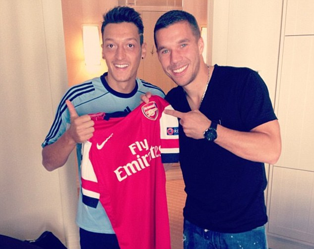 Pals: Ozil and Lukas Podolski pose with an Arsenal shirt while with the Germany squad