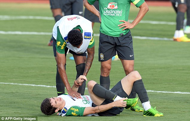 Crocked: Brazil's Oscar gestures on the ground during training that he has been injured