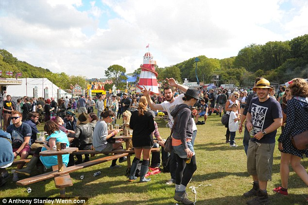 Revellers enjoy the occasional spot of sunshine today at the second day of Bestival on the Isle of Wight
