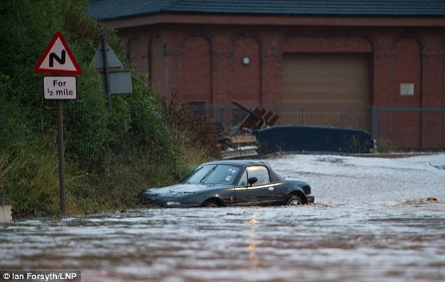 A car is washed down the road in  Saltburn, Cleveland, after persistent heavy rain caused flash flooding
