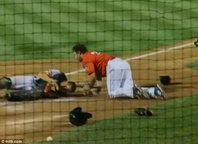 Determined: As Jeroloman remains dazed, Douglas (red) crawls towards home plate in order to score his home run