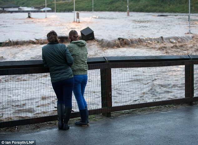 Two women look on as heavy flooding tears through Saltburn in Cleveland yesterday