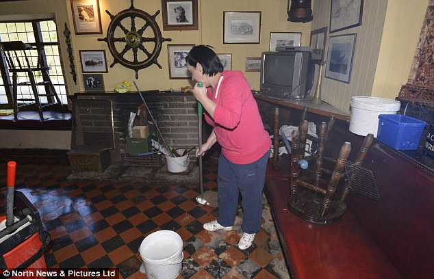 Clean up: A woman mops the floor of her flooded pub in Saltburn-by-the-Sea, East Cleveland after parts of the town were devastated by flooding last night