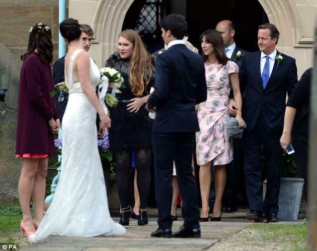 Mingling: Prime Minister David Cameron and his wife Samantha (pictured to the right of the image) are seen with other guests and the bride and groom outside the church