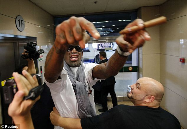 Making an entrance: Dennis Rodman gestures to journalists as he returns to Beijing after his five-day visit to North Korea