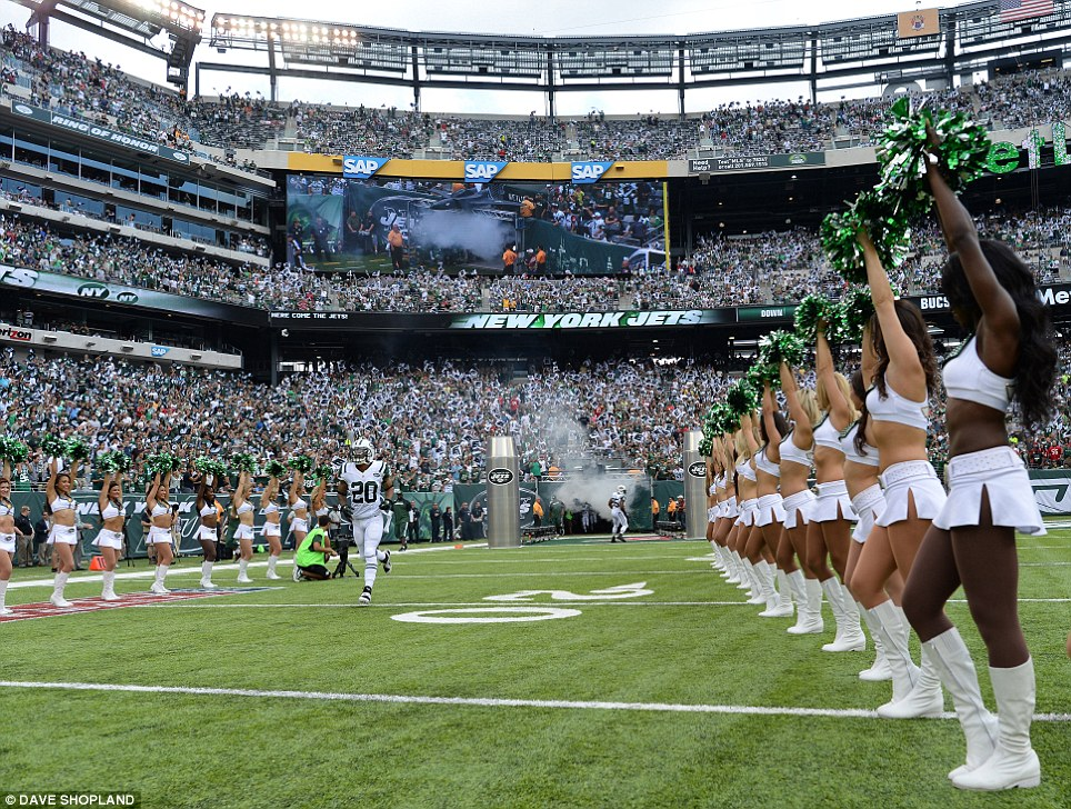 Here they come: Cheerleaders and spectators welcome the New York Jets onto the field for the first time in the 2013 season