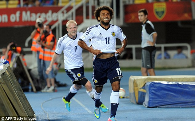 Uncontrolled glee: Scotland's Ikechi Anya (right) and Steven Naismish (left) celebrate after the opener